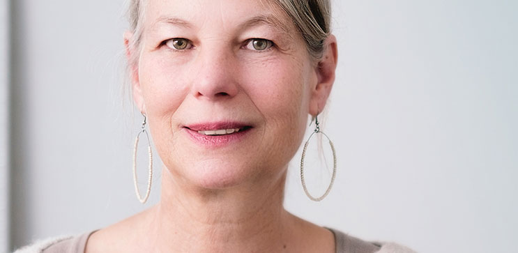 Picture of older woman with hoop earrings smiling to partially reveal her upper teeth