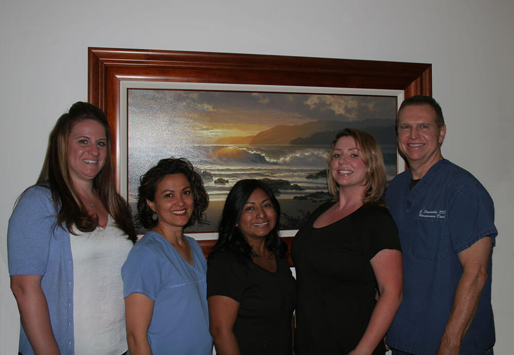 Photograph of Dr. Stockdale and four team members standing in front of a portrait of waves crashing on a beach