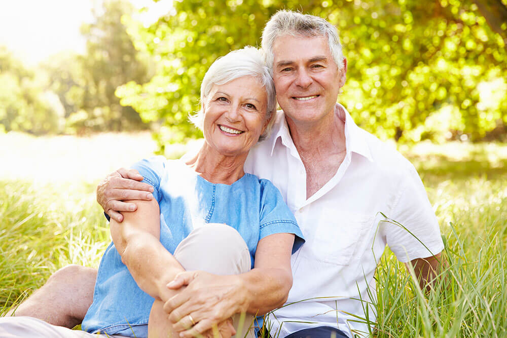 Smiling older couple sitting in a grassy field with trees in the background