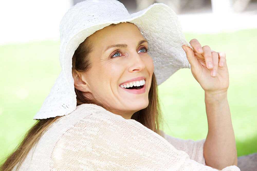 Smiling blue-eyed, blonde woman outdoors wearing white hat and white top