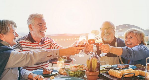 two older couples having dinner together and cheering with wine glasses